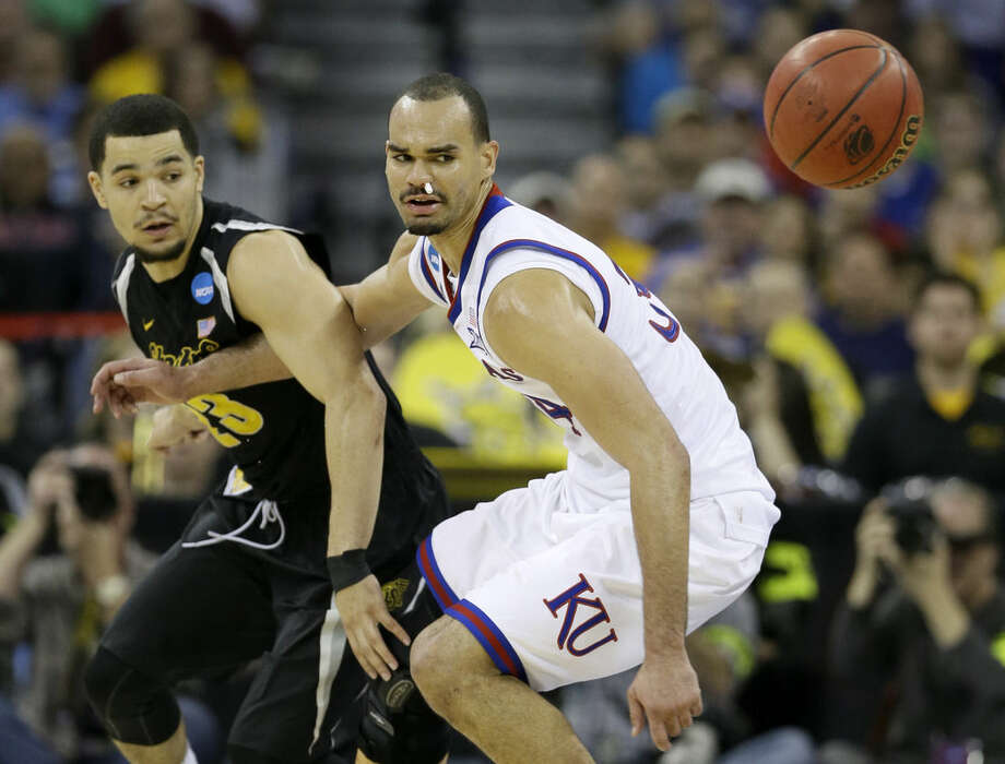 Wichita State guard Fred VanVleet, left, fights for the ball with Kansas forward Perry Ellis during the first half of an NCAA college basketball tournament round of 32 game, Sunday, March 22, 2015, in Omaha, Neb. (AP Photo/Charlie Neibergall)