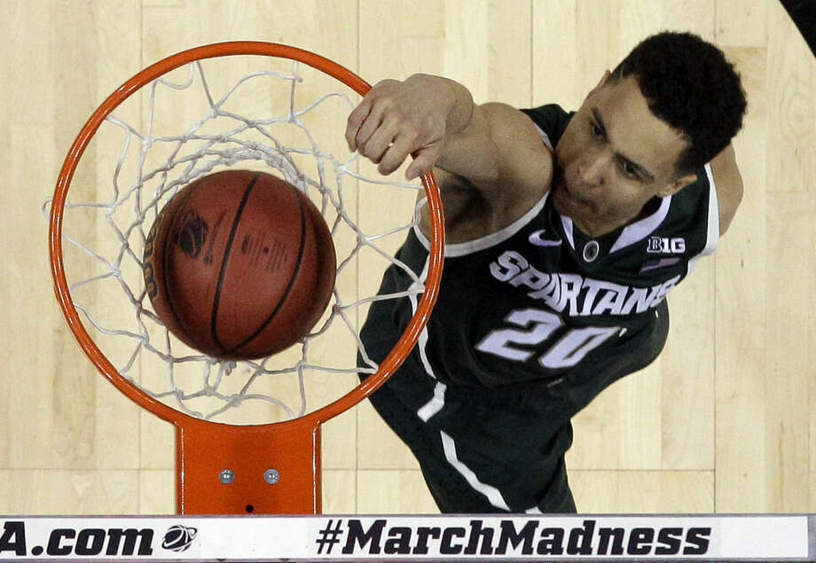 Michigan State's Travis Trice (20) dunks against Virginia during the first half of an NCAA tournament college basketball game in the Round of 32 in Charlotte, N.C., Sunday, March 22, 2015. Michigan State won 60-54. (AP Photo/Gerald Herbert)