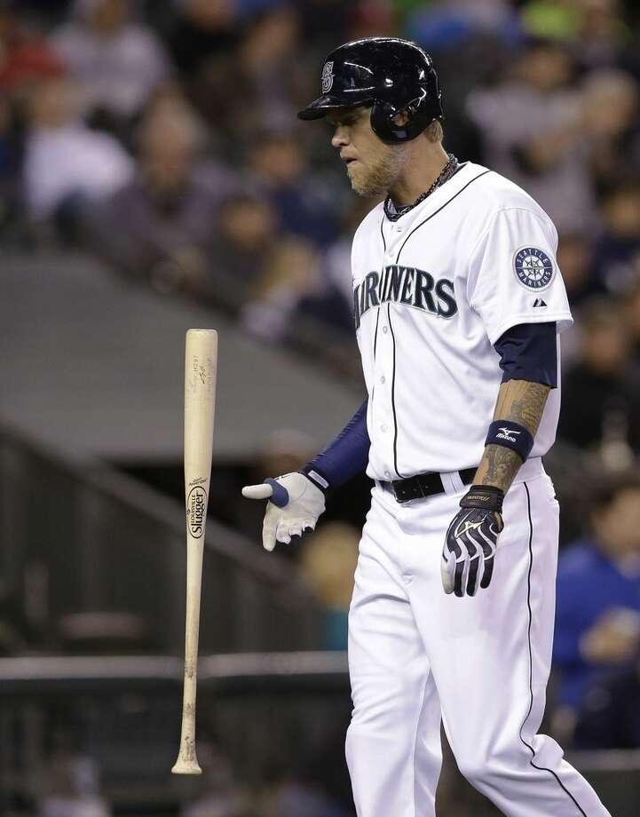 FILE - In this April 9, 2014, file photo, Seattle Mariners' Corey Hart flips his bat as he heads to the dugout after striking out against the Los Angeles Angels in the ninth inning of a baseball game in Seattle. The company that makes Louisville Slugger bats has announced a deal to sell the iconic brand to rival Wilson Sporting Goods Co. Wilson's deal to acquire the global brand, sales and innovation rights from Louisville Slugger's parent, Hillerich & Bradsby Co., still requires approval by H&B shareholders. Under terms of the agreement announced Monday, March 23, 2015, H&B will become Wilson's exclusive manufacturing partner for wood bats. H&B will continue to manufacture wood bats at its factory in Louisville, Kentucky. (AP Photo/Elaine Thompson, File)