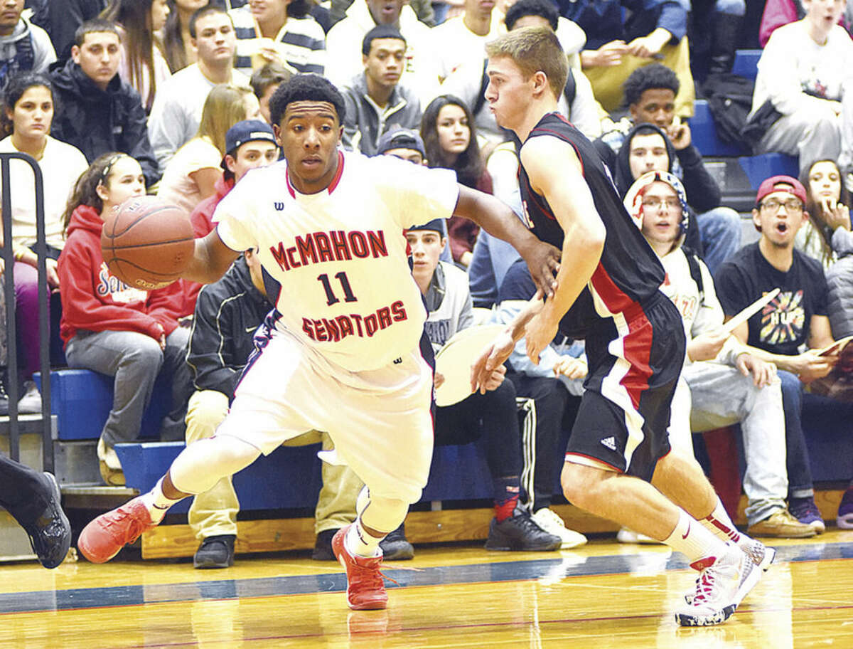 Hour photo/John Nash - McMahon's Jahmerikah Green-Younger drives past a Cheshire defender during Monday's season-opening game in Norwalk.