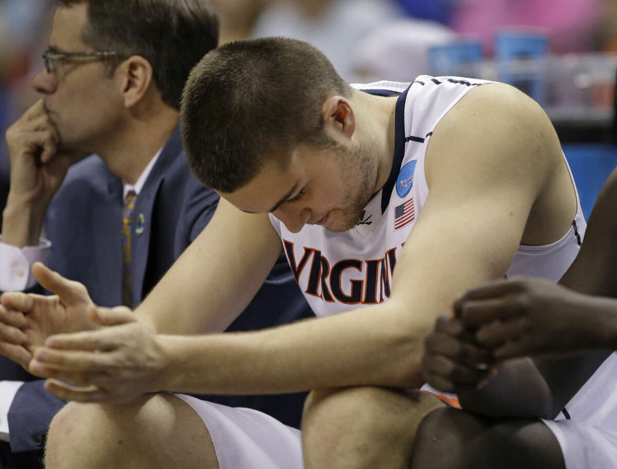 Virginia's Mike Tobey sits on the bench in the final moments during the second half of an NCAA tournament college basketball game against Michigan State in the Round of 32 in Charlotte, N.C., Sunday, March 22, 2015. Michigan State won 60-54. (AP Photo/Gerald Herbert)