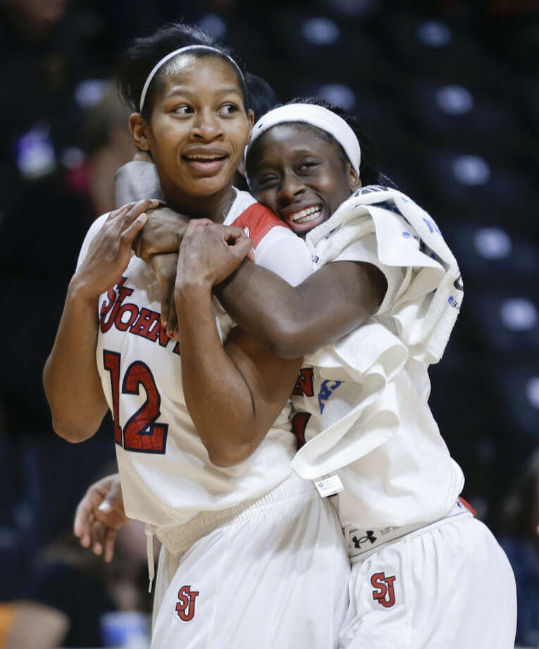 St. John's guard Briana Brown (12) is hugged by Aaliyah Lewis, right, as they leave the court after St. John's defeated Southern California 71-68 in an NCAA women's college basketball first-round tournament game Saturday, March 22, 2014, in Knoxville, Tenn. Brown hit a 3-point shot to give St. John's the win. (AP Photo/Mark Humphrey)