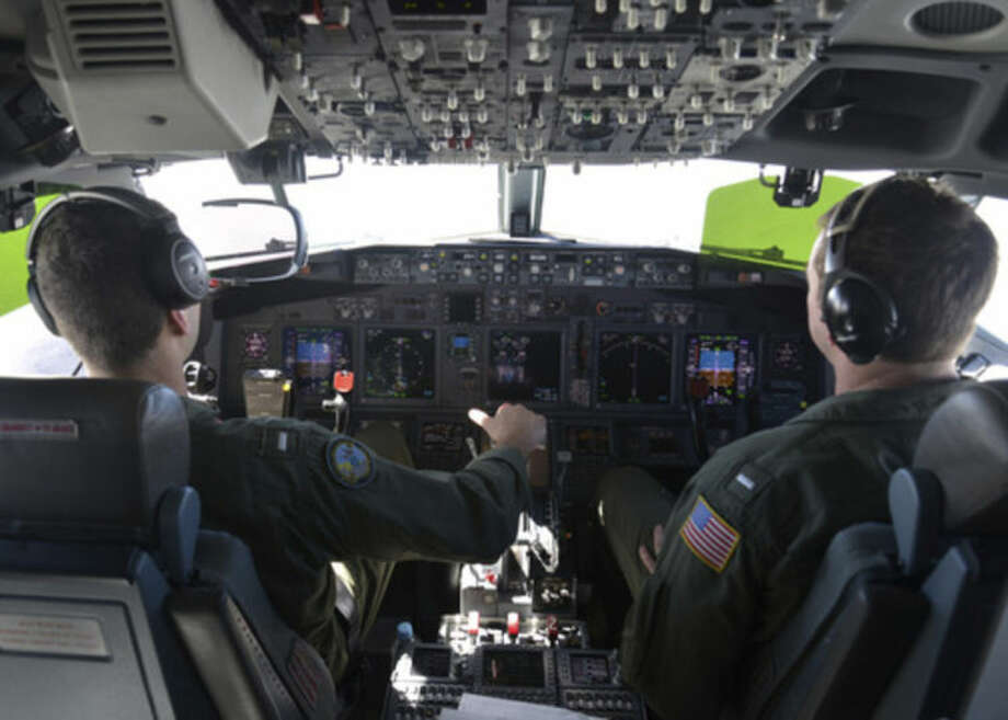 In this photo provided by the U.S. Navy, Lt. j.g. Kyle Atakturk, left, and Lt. j.g. Nicholas Horton, pilot a U.S. Navy P-8A Poseidon during a mission to assist in search and rescue operations for Malaysia Airlines flight MH370 Wednesday March 19, 2014. Military planes from Australia, the U.S. and New Zealand have been searching for the plane in a region over the southern Indian Ocean that was narrowed down from 600,000 square kilometers (232,000 square miles) to 305,000 square kilometers (117,000 square miles). (AP Photo/US Navy, Mass Communication Specialist 2nd Class Eric A. Pastor)