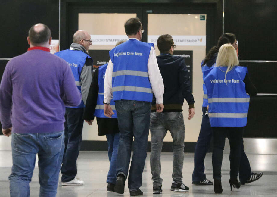 Airport staff walk to a non-public area where people waiting for the Germanwings flight from Barcelona have been brought at the airport in Duesseldorf, Germany, Tuesday, March 24, 2015, after a Germanwings passenger jet carrying 148 people crashed in the French Alps region as it traveled from Barcelona to Duesseldorf. (AP Photo/Frank Augstein)