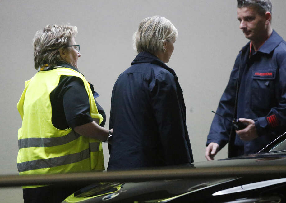A woman waiting for flight 4U 9525 is lead away by airport staff at the airport in Duesseldorf, Germany, Tuesday, March 24, 2015, after a Germanwings passenger jet carrying more than 140 people crashed in the French Alps region as it traveled from Barcelona to Duesseldorf. (AP Photo/Frank Augstein)