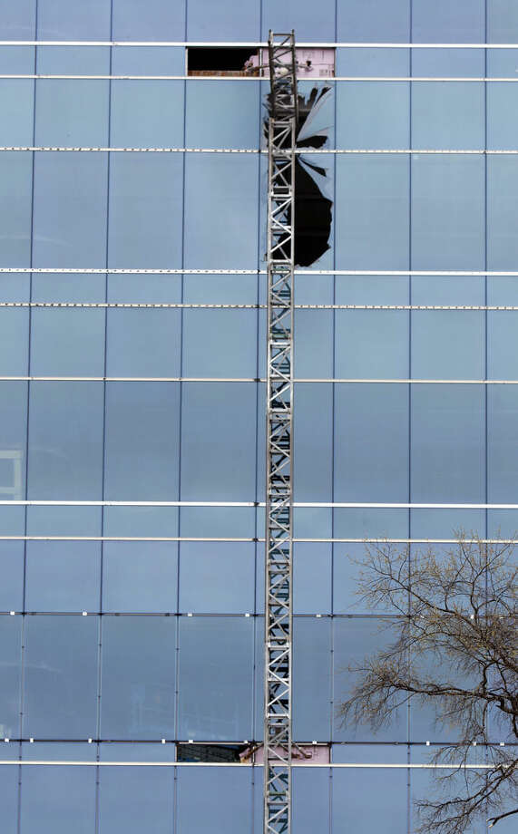 A section of scaffolding framework hangs from the side of the Charter Square building at the scene of a construction accident in downtown Raleigh, NC that killed three people and sent another to a hospital, Monday, March 23, 2015. A scaffolding holding at least three workers fell and crashed into the Charter Square project, an 11-story building being built on the south end of Fayetteville Street. (AP Photo/The News & Observer, Harry Lynch)