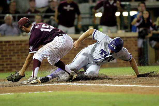 TCU's Luken Baker (19) is called safe at home after a wild pitch as Texas A&M's Brigham Hill (15) tries to apply a tag during the fifth inning of an NCAA Super Regional baseball tournament game, Friday, June 10, 2016, in College Station, Texas. (AP Photo/Sam Craft)