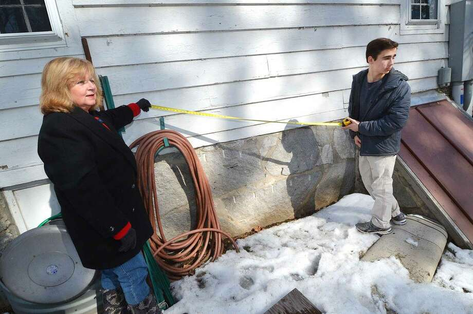 Hour Photo/Alex von Kleydorff Wilton Garden Club member Ann Collins and Project manager Nicholas Johnson measure forn a new Neighborhood Garden tool shed to be built at Trackside Teen Center in Wilton