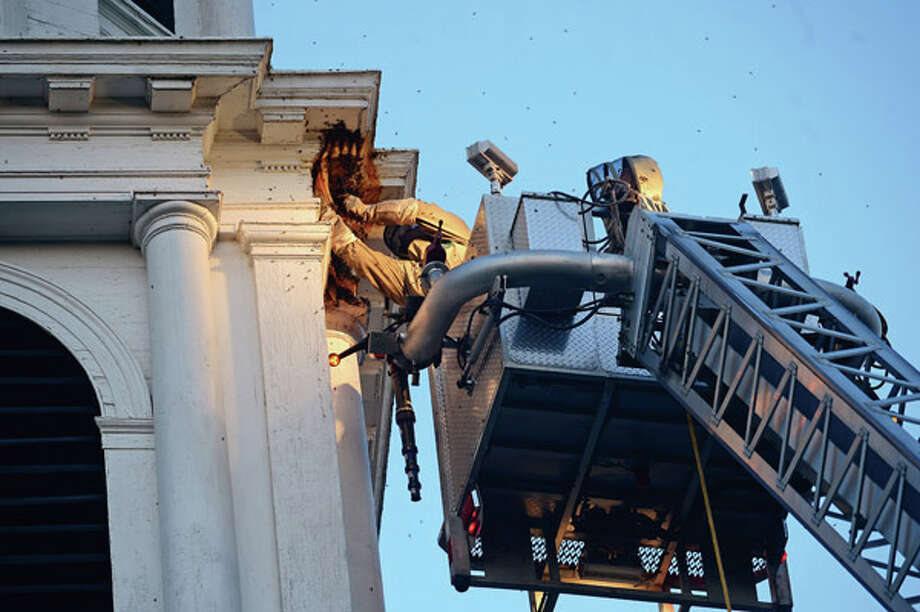 Beekeepers Andrew and Norm Cote rescue a hive of honey bees that had nested in the eaves of the steeple of the First Cogregational Church on the Green in Norwalk. Hour photo / Erik Trautmann / (C)2012, The Hour Newspapers, all rights reserved