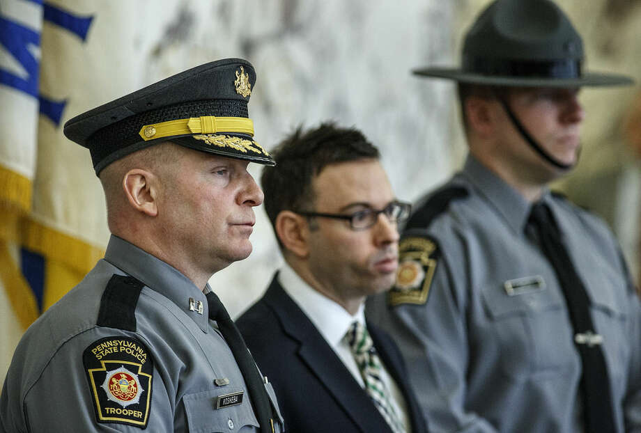As Dauphin County District Attorney Ed Marsico speaks, Pennsylvania state police Troop H Capt. Adam Kosheba, left, Deputy District Attorney John Baer, center, and state police spokesman Trooper Robert Hicks stand behind him during a news conference Tuesday, March 24, 2015, in Harrisburg. Pa., regarding the shooting death of an unarmed man after a traffic stop by police. Authorities filed the charge of criminal homicide Monday, against 36-year-old Hummelstown Police Office Lisa Mearkle, saying she shot David Kassick twice in the back as he lay facedown on the ground. (AP Photo/PennLive.com, Dan Gleiter)