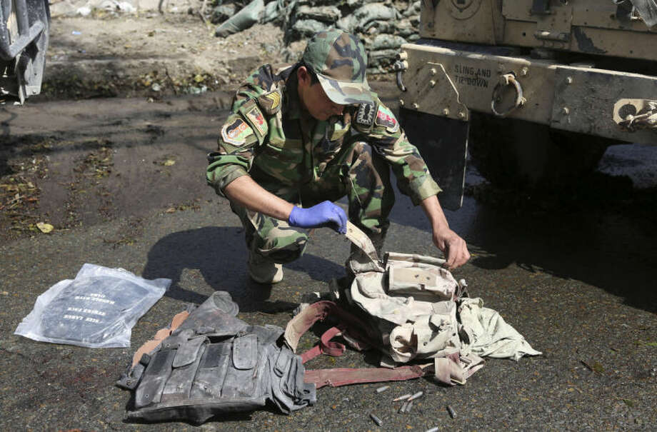 An Afghan Army soldier goes through bullet proved vests found after Taliban insurgents staged a multi-pronged attack on a police station in Jalalabad, eastern Afghanistan, Thursday, March 20, 2014. Taliban insurgents staged the attack, using a suicide bomber and gunmen to lay siege to the station, government officials said. Two remotely detonated bombs also exploded nearby. (AP Photo/Rahmat Gul)