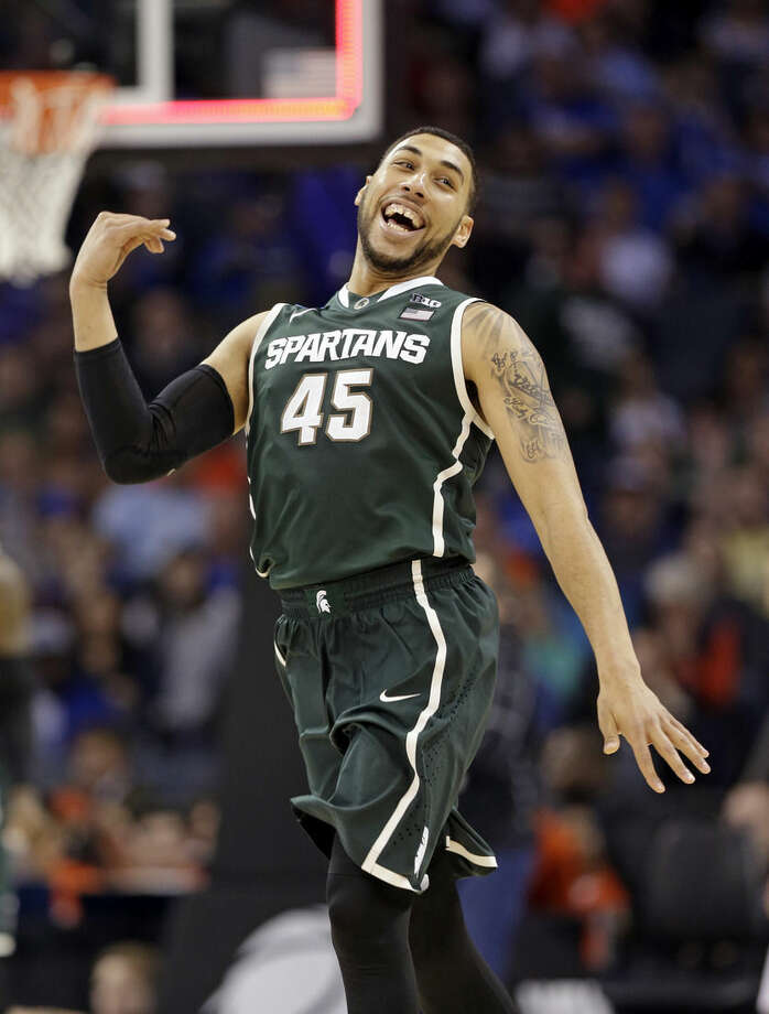 Michigan State's Denzel Valentine (45) celebrates at the end of an NCAA tournament college basketball game against Virginia in the Round of 32 in Charlotte, N.C., Sunday, March 22, 2015. Michigan State won 60-54. (AP Photo/Nell Redmond)