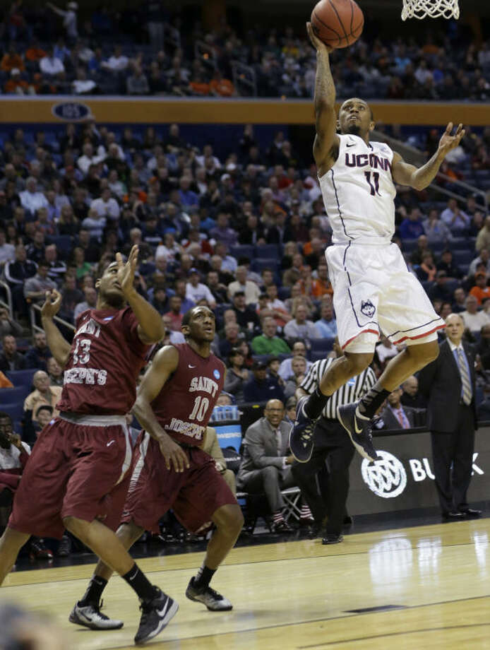 Connecticut's Ryan Boatright (11) drives past Saint Joseph's Ronald Roberts Jr. (13) and Langston Galloway (10) during the first half of a second-round game in the NCAA college basketball tournament in Buffalo, N.Y., Thursday, March 20, 2014. (AP Photo/Frank Franklin II)