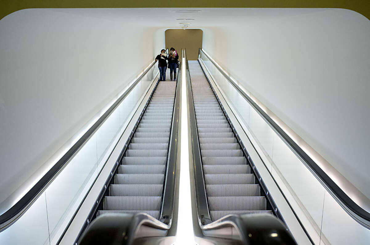 Two visitors take an escalator after attending a press preview of the exhibit