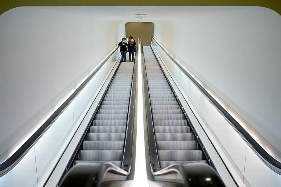 "Two visitors take an escalator after attending a press preview of the exhibit ""The Oasis of Matisse"" at Stedelijk Museum in Amsterdam, Netherlands, Wednesday, March 25, 2015. The exhibit with over 100 loaned pictures opens for the public on Friday March 27 and runs till Aug. 16, 2015. (AP Photo/Peter Dejong)"