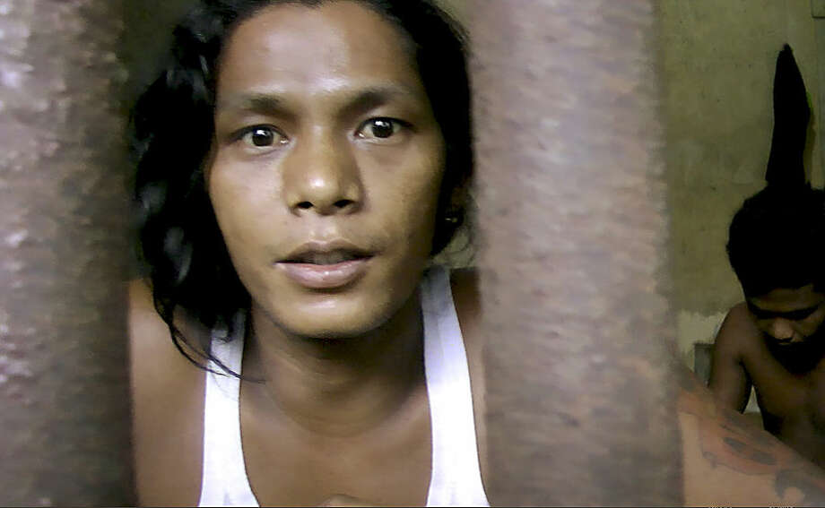 """In this Thursday, Nov. 27, 2014 image from video, Kyaw Naing, a slave from Myanmar, looks through the bars of a cell at the compound of a fishing company in Benjina, Indonesia. After working for three years on a Thai trawler, sometimes enduring beatings with the bones of sting ray, he begged his captain to let him return home. """"All I did was tell my captain I couldn't take it anymore, that I wanted to go home,"""" Naing says. """"The next time we docked, I was locked up."""" (AP Photo/APTN)"""