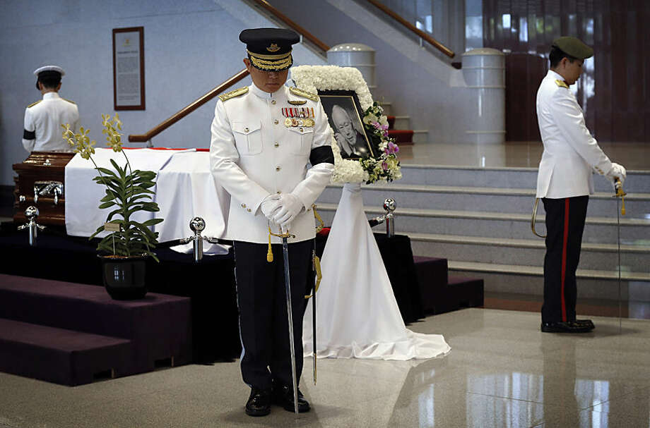 Vigil guards stand with their ceremonial swords inverted, around the coffin of the late Lee Kuan Yew at the Parliament House where he will lie in state for four days, Wednesday, March 25, 2015, in Singapore. Singapore mourned longtime leader Lee with raw emotion and a blanket of relentlessly positive coverage on its tightly scripted state television on Monday, mythologizing a man who was as respected as he was feared. (AP Photo/Wong Maye-E)