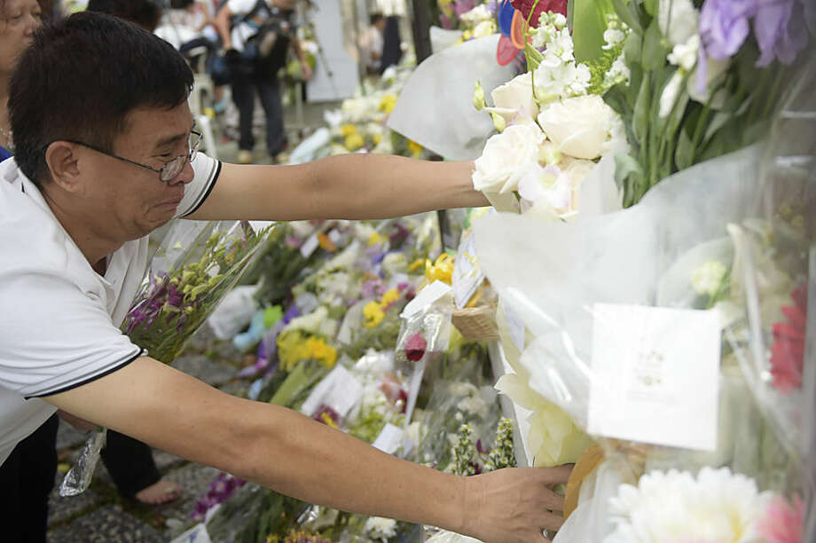 Mourner Chew Lian San breaks down as he tries to arrange flowers at the gate of Istana or presidential palace, in Singapore Tuesday, March 24, 2015, a day after the death of Singapore's founding father Lee Kuan Yew. Singapore mourned longtime leader Lee with raw emotion and a blanket of relentlessly positive coverage on its tightly scripted state television on Monday, mythologizing a man who was as respected as he was feared. (AP Photo/Joseph Nair)