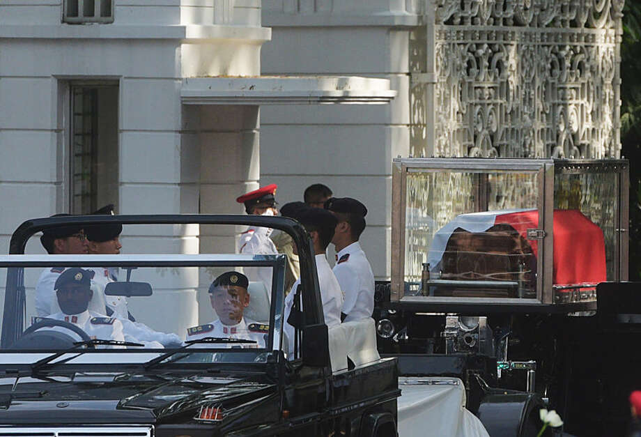 The coffin of Singapore's founding father Lee Kuan Yew leaves Istana, or Presidential Palace on a ceremonial gun carriage to lie in state at parliament, Wednesday, March 25, 2015 in Singapore. (AP Photo/Joseph Nair)