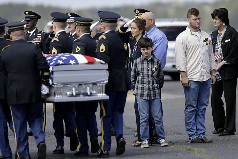 The casket of Louisiana Air National Guard Chief Warrant Officer George David Strother is carried past family during a deplaning ceremony at Louisiana Air National Guard Army Aviation Support Facility #2 at Esler Field in Pineville, La., Tuesday, March 24, 2015. Second right is D.J. Strother, his son, who served in the Guard with him. Strother was killed along with three other Guardsmen and seven Marines in a helicopter crash during a training exercise off the coast of Florida on March 10, 2015. (AP Photo/Gerald Herbert)
