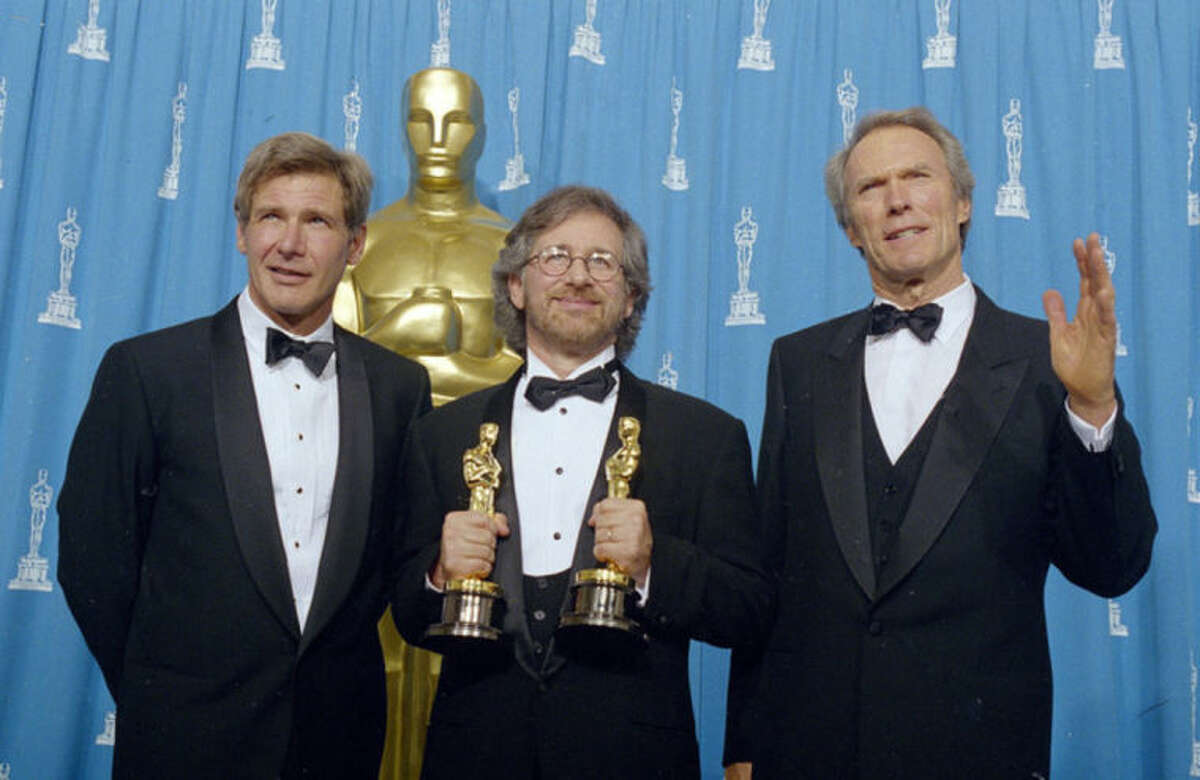 FILE - This March 21, 1994 file photo shows, director Steven Spielberg, center, with actor Harrison Ford, left, and actor and director Clint Eastwood at the 66th Annual Academy Awards, in Los Angeles. Spielberg won best director and best picture for his film,