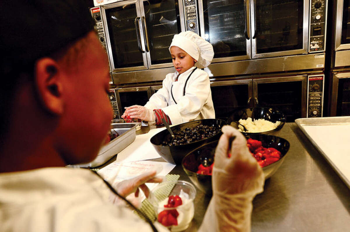 Hour photo / Erik Trautmann 7 year Tylor Baez, right, takes part in Whitsons School Nutrition and Norwalk Public School's Chefology 101 student culinary program Thursday at Central Kitchen.