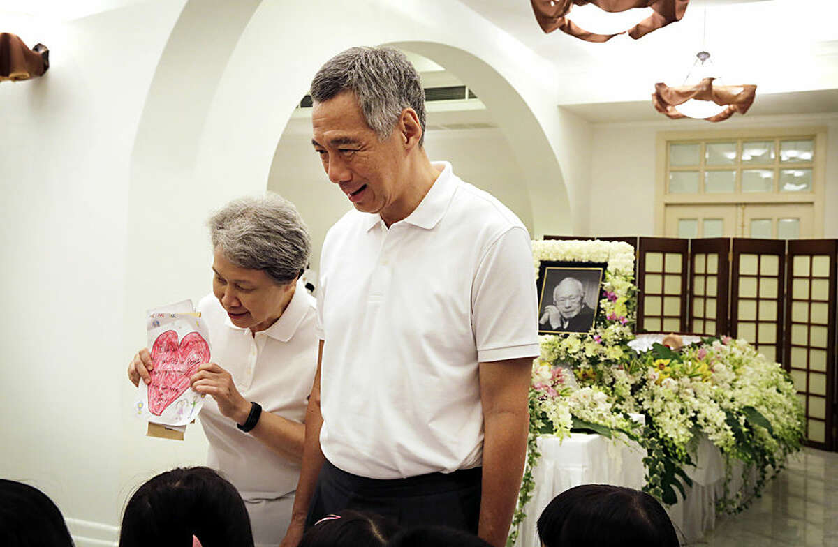 Singapore Prime Minister Lee Hsien Loong and his wife Ho Ching, left, talk to pre-school children who presented them with a drawing of a heart as they come to pay their respects to the late Lee Kuan Yew during a private family wake at the Istana, or Presidential Palace, Tuesday, March 24, 2015, in Singapore. Singapore mourned longtime leader Lee with raw emotion and a blanket of relentlessly positive coverage on its tightly scripted state television on Monday, mythologizing a man who was as respected as he was feared. (AP Photo/Wong Maye-E)