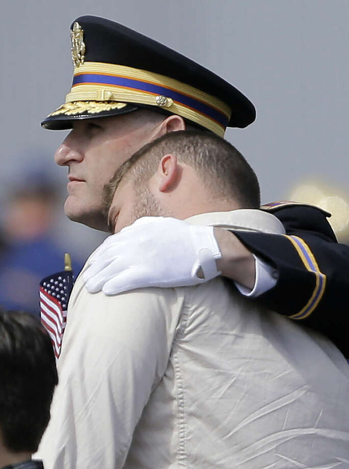 D.J. Strother, foreground, is comforted by Louisiana National Guard Maj. Gen. Glenn H. Curtis, during a deplaning ceremony for the casket of his father, Chief Warrant Officer George David Strother, at Louisiana Air National Guard Army Aviation Support Facility #2 at Esler Field in Pineville, La., Tuesday, March 24, 2015. The father and son served in the Guard together. Strother was killed along with three other Guardsmen and seven Marines in a helicopter crash during a training exercise off the coast of Florida March 10, 2015. (AP Photo/Gerald Herbert)