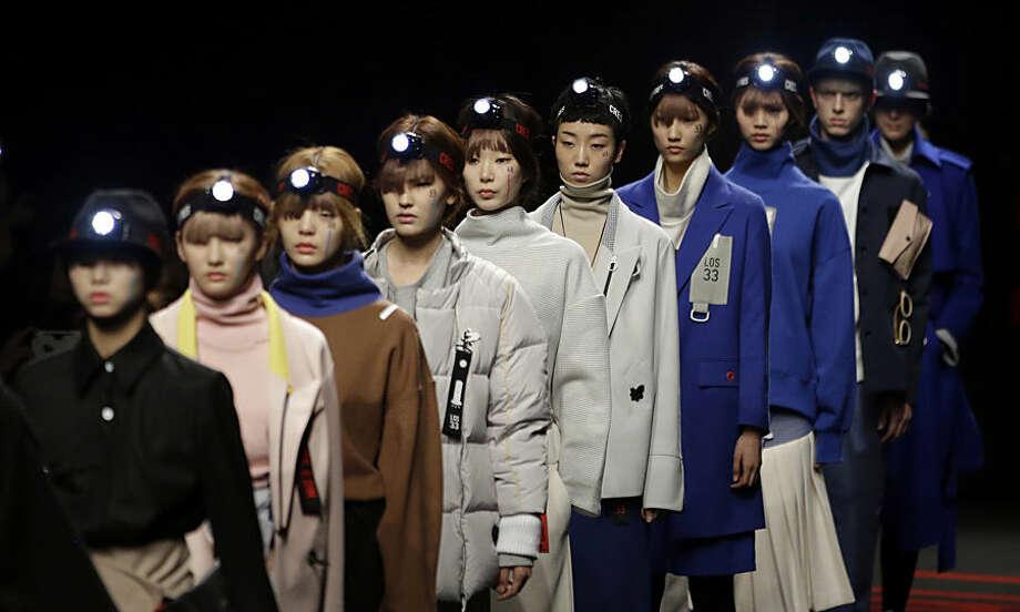 Models display creation by South Korean fashion designer Hongbum Kim during the 2015 fall/winter show at the Seoul Fashion Week in Seoul, South Korea, Tuesday, March 24, 2015. (AP Photo/Lee Jin-man)