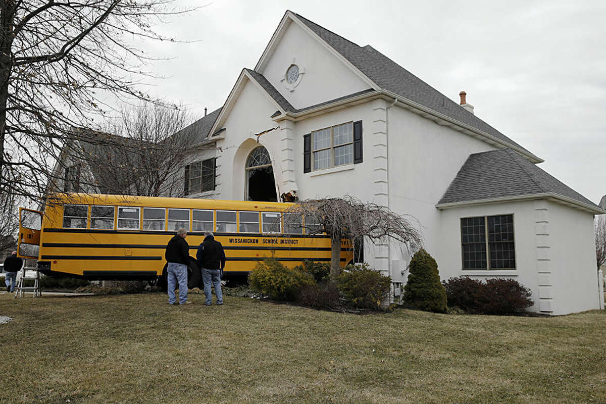 Men inspect a school bus that crashed into a home Tuesday morning, March 24, 2015, in Blue Bell, Pa. Officials say nine students from St. Helena School were aboard, but none were injured, when the bus slammed into the suburban Philadelphia home around 7:45 a.m. Officials say the bus driver was taken to Abington Hospital. People inside the home were not hurt. (AP Photo/Matt Rourke)