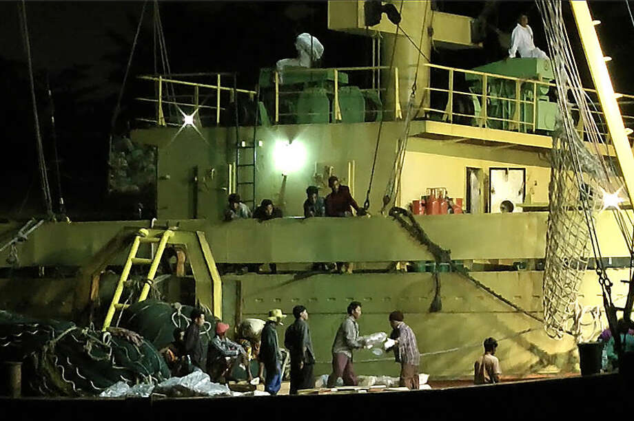 In this Thursday, Nov. 27, 2014 image from video, workers from Myanmar load fish onto a Thai-flagged cargo ship in Benjina, Indonesia. An intricate web of connections separates the fish we eat from the men who catch it, and obscures a brutal truth: Your seafood may come from slaves. (AP Photo/APTN)