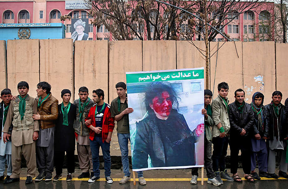 "Afghan men stand in front of the supreme court during a protest demanding justice for a woman who was beaten to death by a mob after being falsely accused of burning a Quran last week, in downtown Kabul, Afghanistan, Tuesday, March 24, 2015. Men and women of all ages carried banners bearing the bloodied face of Farkhunda, a 27-year-old religious scholar killed last week by a mob. Farkhunda, who went by one name like many Afghans, was beaten, run over with a car and burned before her body was thrown into the Kabul River. The poster with Farkhunda's photo on it with Persian writing reads, ""we want justice."" (AP Photo/Massoud Hossaini)"