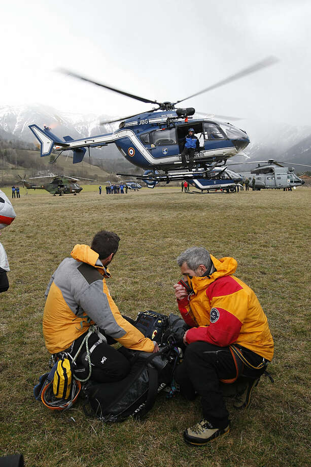 Rescue workers watch a rescue helicopter taking off from Seyne-les-Alpes, French Alps, Tuesday, March 24, 2015. A Germanwings passenger jet carrying 150 people crashed Tuesday in the French Alps as it flew from Barcelona to Duesseldorf, authorities said. (AP Photo/Claude Paris)
