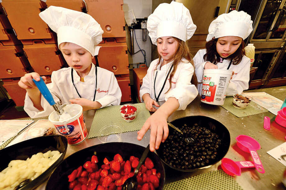 Hour photo / Erik Trautmann Wolfpit student Henry Bustell, Jefferson student Isabella Papadopoulos and Marvin student Mia Sclaeger take part in Whitsons School Nutrition and Norwalk Public School's Chefology 101 student culinary program Thursday at Central Kitchen.