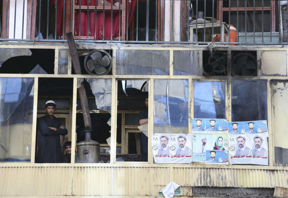 An Afghan man peers through broken glass windows of a building after a multi-pronged attack on a police station in Jalalabad, the capital of eastern Nangarhar province, Afghanistan, Thursday, March 20, 2014. Taliban insurgents staged the attack, using a suicide bomber and gunmen to lay siege to the station, government officials said. Two remotely detonated bombs also exploded nearby. (AP Photo/Rahmat Gul)