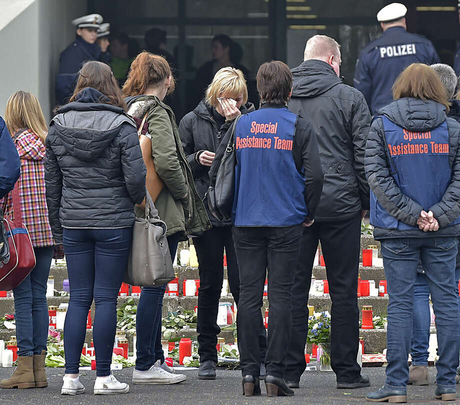 Students, teachers and relatives mourn in front of a school in Haltern, western Germany, Wednesday, March 25, 2015, one day after 16 school children and two teachers were among the 150 victims that died in the Germanwings plane crash in the French alps on the way from Barcelona to Duesseldorf. (AP Photo/Martin Meissner)