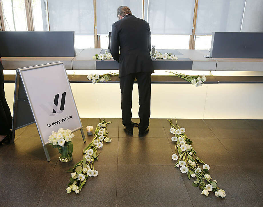 A Lufthansa employee signs in a condolence book in Frankfurt, Germany, Wednesday, March 25, 2015, for the 150 victims that died in the Germanwings plane crash in the French alps on the way from Barcelona to Duesseldorf on Tuesday. (AP Photo/Michael Probst)