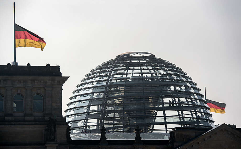 German flags fly on half-staff on the roof of the Reichstag, the parliament building, in Berlin, Germany, Wednesday March 25, 2015, the day after a Germanwings aircraft crashed in France on the way from Barcelona, Spain, to Duesseldorf, Germany, killing 150 people. (AP Photo/dpa,Bernd Jutrczenka) (AP Photo/dpa,Bernd Jutrczenka)