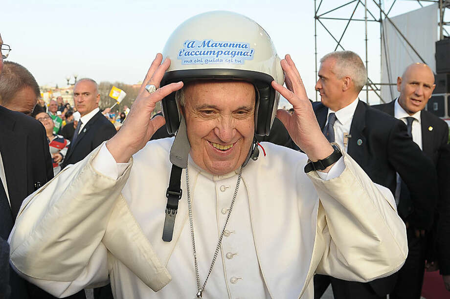 In this March 21, 2015 pool photo, made available Monday, March 23, 2015, Pope Francis wears a helmet as he meets youths in Naples, Italy. Pope Francis made an impassioned defense of the unemployed during a speech to people in the poor Neapolitan neighborhood of Scampia Saturday. (AP Photo/L'Osservatore Romano, Pool)