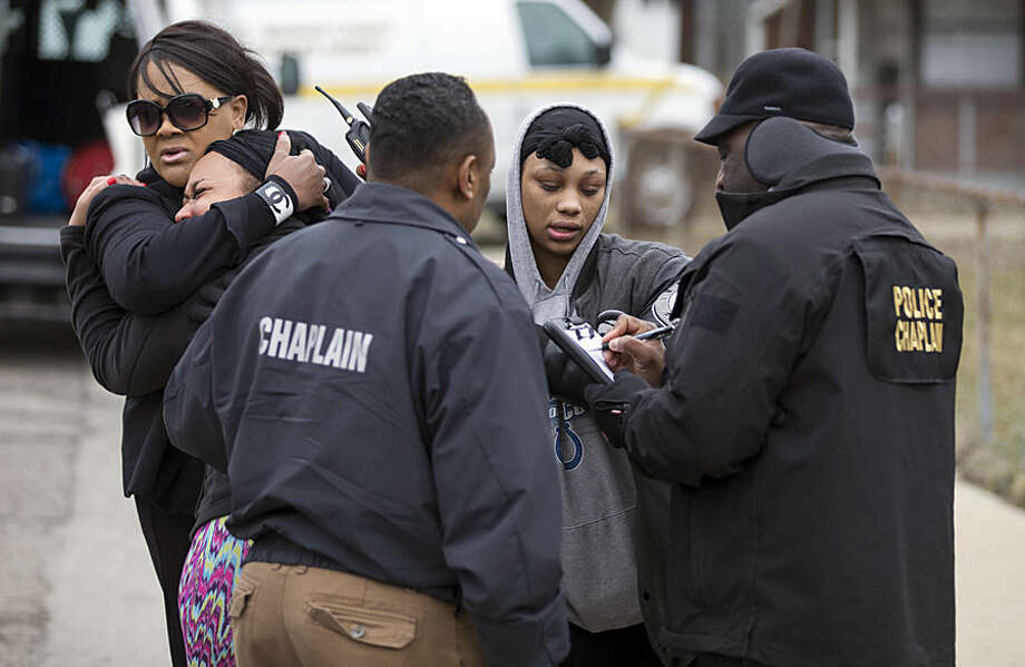 Indianapolis Metropolitan Police, including Chaplains, conduct interviews as they investigate the scene of a shooting, Tuesday, March 24, 2015, in Indianapolis. Indianapolis Police Chief Rick Hite says three women and a man have been shot to death. Hite says the shootings don't appear random and likely occurred Tuesday morning. (AP Photo/The Indianapolis Star, Robert Scheer)