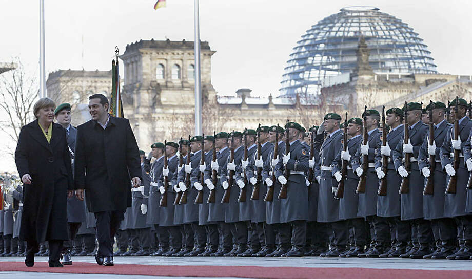 German Chancellor Angela Merkel, left, welcomes the Prime Minister of Greece Alexis Tsipras, right, with military honors at the chancellery in Berlin, Germany, Monday, March 23, 2015. Building in the background is the Reichstag that hosts the German parliament. (AP Photo/Michael Sohn)