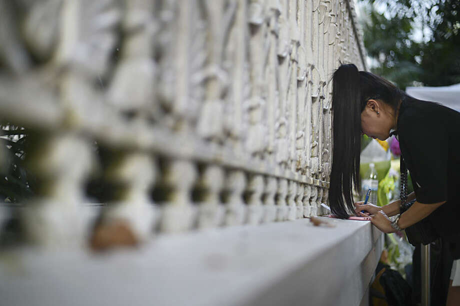 A mourner writes a condolence message at Istana, or Presidential Palace, where a private wake for the late Lee Kuan Yew is being held, in Singapore Tuesday, March 24, 2015. Singapore mourned longtime leader Lee with raw emotion and a blanket of relentlessly positive coverage on its tightly scripted state television on Monday, mythologizing a man who was as respected as he was feared. (AP Photo/Joseph Nair)