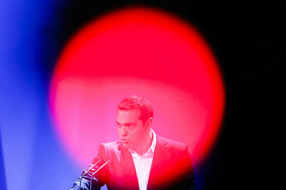 In this photo taken with a red television camera control light in the foreground, the Prime Minister of Greece Alexis Tsipras briefs the media on a news conference during a bilateral meeting with German Chancellor Angela Merkel at the chancellery in Berlin, Monday, March 23, 2015. (AP Photo/Markus Schreiber)