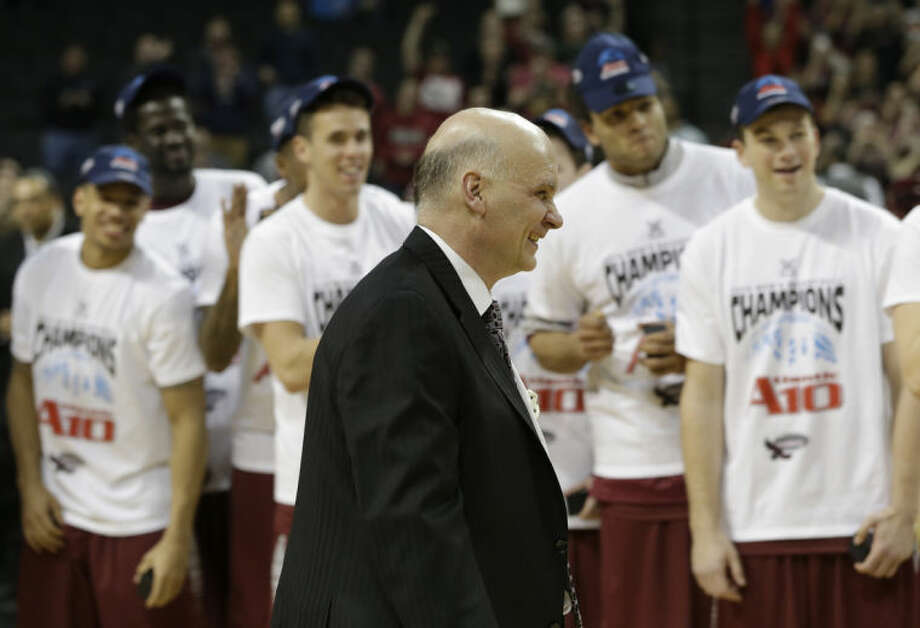 While his team watches, Saint Joseph head coach Phil Martelli smiles during an awards ceremony after an NCAA college basketball game against VCU in the championship round of the Atlantic 10 Conference tournament at the Barclays Center in New York, Sunday, March 16, 2014. St. Joseph's defeated VCU 65-61. (AP Photo/Seth Wenig)