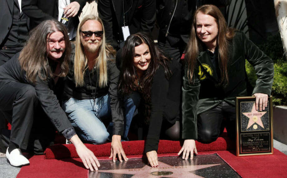 "FILE - In this Jan. 29, 2010 file photo, rock and roll legend Roy Orbison is honored with a star posthumously on the Hollywood Walk of Fame, with family members, from left, sons Wesley, Alex, wife Barbara Orbison, and Roy Jr. in the Hollywood section of Los Angeles. Orbison's three sons are all musicians but never really got to play music with their dad - until now. Wesley, Roy Jr. and Alex Orbison have helped create a new song by their father that will appear on the 25th anniversary reissue and expansion of Orbison's final album, ""Mystery Girl"" that is being re-released on May 20, 2014. (AP Photo/Nick Ut, file)"