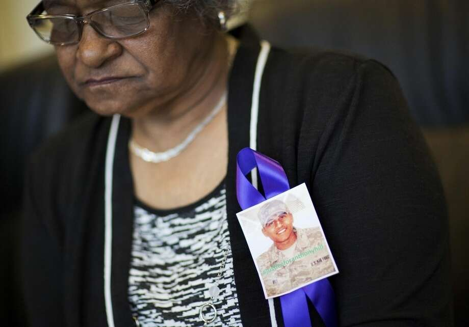 Theola Baylor wears a ribbon memorializing her grandson Anthony Hill, a naked, mentally ill man who was fatally shot by a police officer, as she sits during an interview Wednesday, March 25, 2015, in Atlanta. An attorney for Hill's family, Christopher Chestnut, says witness statements suggest DeKalb County police officer Robert Olsen could have retreated before fatally shooting Hill, 26, on March 9 while responding to a call reporting a suspicious person knocking on doors and crawling naked on the ground. (AP Photo/David Goldman)