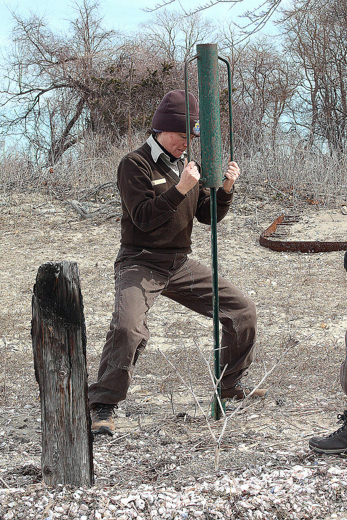 Hour photo/Chris Bosak U.S. Fish and Wildlife biologist Kris Vagos digs a hole for a polel on Chimon Island on Wednesday. The U.S. Fish & Wildlife officials were on the island to mark off areas to protect a bald eagle nest.