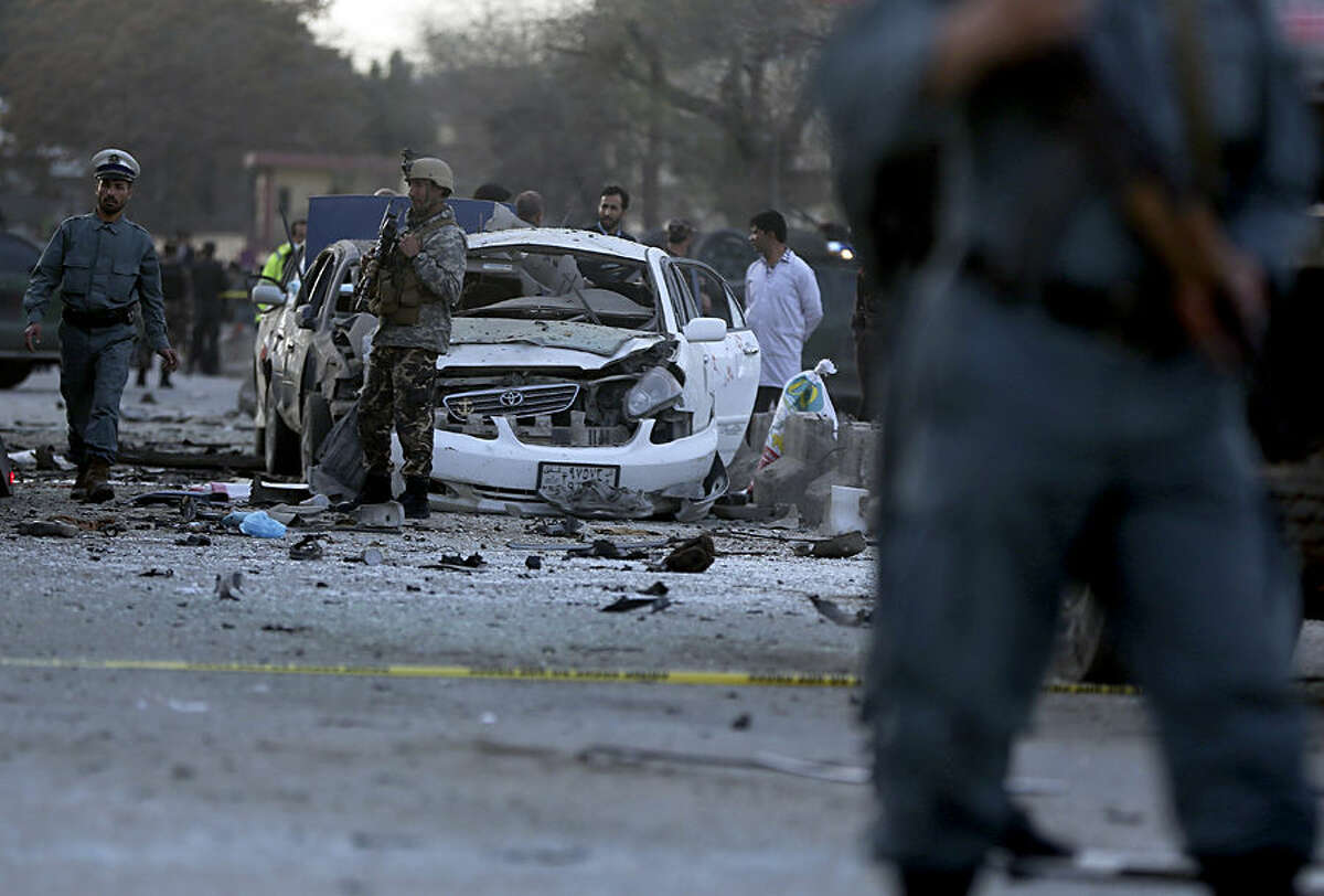 Afghanistan's security forces inspect the site of a suicide attack in Kabul, Afghanistan, Wednesday, March 25, 2015. The suicide car bombing in the heart of the Afghan capital killed several people and wounded tens, according to Afghan security officials. (AP Photo/Massoud Hossaini)