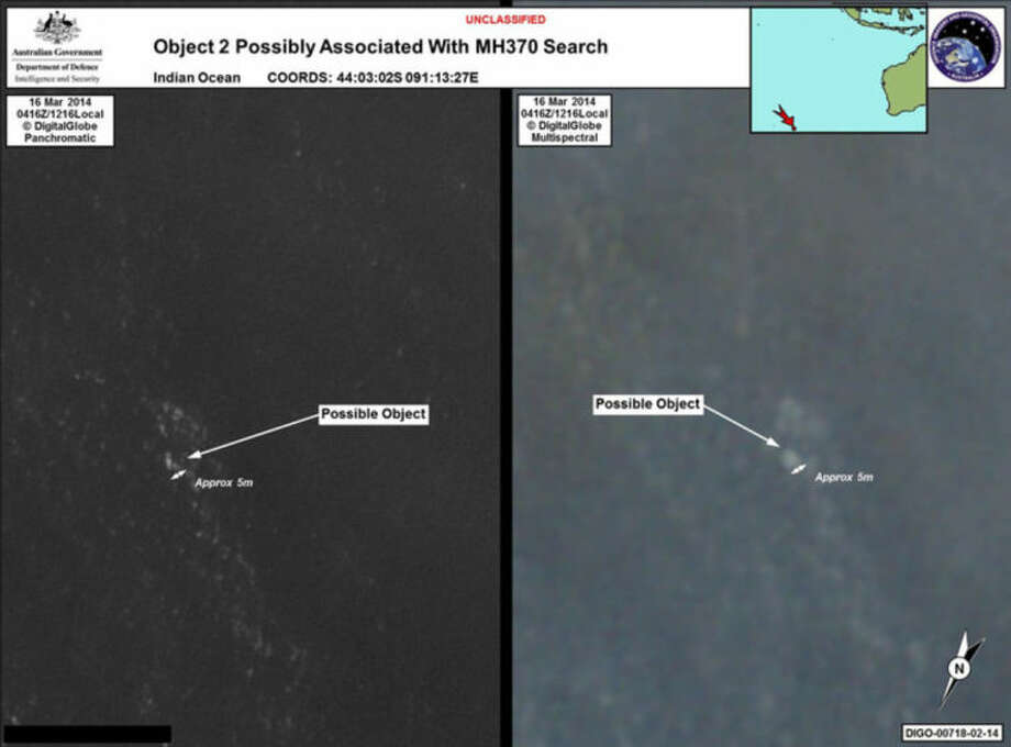 In this March 16, 2014 satellite imagery provided by Commonwealth of Australia - Department of Defence on Thursday, March 20, 2014, a floating object is seen at sea next to the descriptor which was added by the source. Australia's government reported Thursday, March 20, 2014 that the images show suspected debris from the missing Malaysia Airlines jetliner floating in an area 2,500 kilometers (1,550 miles) southwest of Perth Australia. (AP Photo/Commonwealth of Australia - Department of Defence)