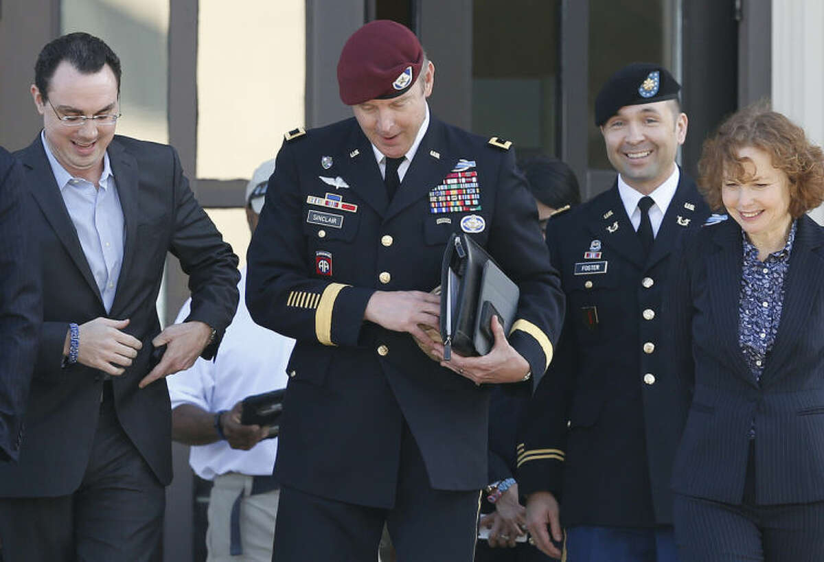 Brig. Gen. Jeffrey Sinclair, center, who admitted to inappropriate relationships with three subordinates, leaves the courthouse after being sentenced at Fort Bragg, N.C., Thursday, March 20, 2014. Attorneys Ellen Brotman, right, and Maj. Sean Foster, along with Josh Zeitz, left, who handled Public Relations for the defense, are by his side. Sinclair was reprimanded and docked $20,000 in pay Thursday, avoiding jail time in one of the U.S. military's most closely watched courts-martial. (AP Photo/Ellen Ozier)